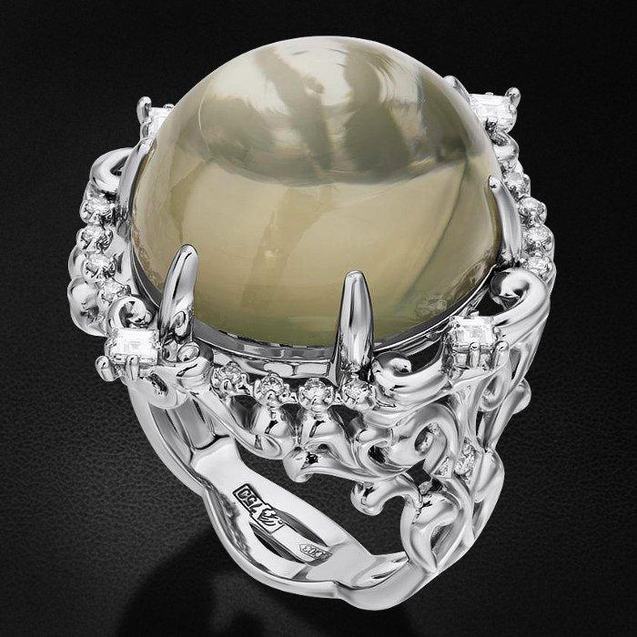 Кольцо с бриллиантами, лунным камнем из белого золота 750 пробыКольца<br>Кольцо с бриллиантами, лунным камнем из белого золота 750 пробы. Характеристики вставок: 2 бриллиант кр57 - 0,03 3/5а, 16 бриллиант кр57 - 0,135 3/5а, 4 бриллиант квадрат - 0,23 2/2а, 1 лунный камень кабошон - 23,01. Средний вес изделия: 15,5 гр.<br>